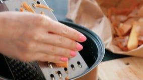 特写镜头妇女` s递在一台磨丝器的磨擦红萝卜在平底深锅 影视素材