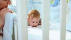 特写镜头妈妈使用与小儿床的一个小小孩笑侧视图的通过小儿床的格子 E 股票视频