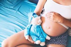 特写镜头孕妇有女用连杉衬裤玩具熊的` s腹部 免版税库存照片
