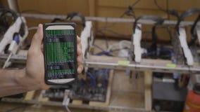 特写镜头它专家手显示开采的bitcoin的藏品智能手机流动应用程序在cryptocurrency船具附近- 影视素材