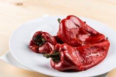 特写镜头宏指令烤了在白色板材供食的新鲜的红色辣椒粉 库存图片