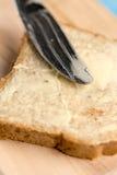 特写镜头宏观面包用在木板的黄油涂有刀子的 库存图片