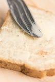特写镜头宏观面包用在木板的黄油涂有刀子的 免版税库存图片
