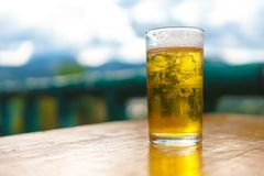 特写镜头射击了一杯在一张木桌上的啤酒与农村na 图库摄影