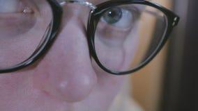 特写镜头射击了在反射一个运转的屏幕的玻璃的妇女眼睛 影视素材