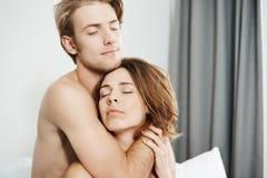 特写镜头射击了在爱的两个美丽的嫩年轻成人,拥抱在与闭合的眼睛和浪漫微笑的床上 夫妇 免版税库存照片