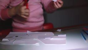 特写镜头射击了小女孩在桃红色毛线衣切口纸板料形状的` s手与在玻璃桌上的剪刀 股票视频