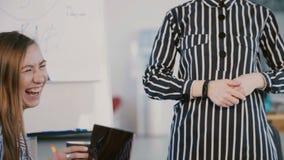 特写镜头射击了提出想法的正式办公室衣裳的妇女在flipchart,谈话与伙伴在现代轻的办公室 股票录像
