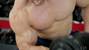特写镜头射击了有做在健身房的强健的身体的大力士哑铃锻炼 股票视频