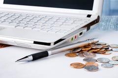 特写镜头射击了有铅笔的硬币膝上型计算机和堆在木桌上的 免版税库存照片
