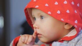 特写镜头射击了蓝眼睛的婴孩面孔观看的动画片 红色敞篷的孩子有银色心脏样式的吮他的 股票视频