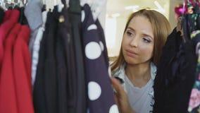 特写镜头射击了衣裳的女学生购物,看通过在挂衣架,接触和移动的五颜六色的服装 影视素材