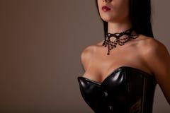 特写镜头射击了黑色束腰的大乳房妇女 免版税库存照片