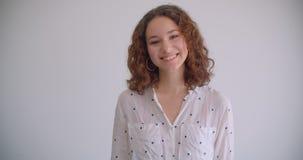 特写镜头射击年轻时髦的长发卷曲白种人女性微笑愉快地看的照相机有背景 股票视频