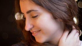 特写镜头射击年轻有吸引力白种人女性微笑诱人地看在的旁边iwith bokeh光 免版税库存照片
