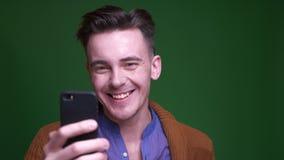 特写镜头射击成人有吸引力manhaving快乐地微笑有背景的电话隔绝在绿色 影视素材