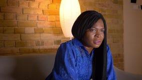 特写镜头射击成人非裔美国人的在电视的女性观看的体育和庆祝与胜利坐长沙发 股票录像
