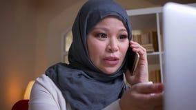 特写镜头射击通过照相机移动成人回教女性employeein hijab快乐地谈话在键入在的电话 股票录像