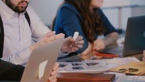 特写镜头射击,拿着关于桌的年轻商人手纸笔记在企业关于建筑学项目的队会议上 股票视频