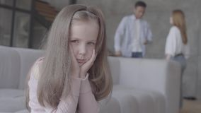 特写镜头小blong哀伤的女孩在沙发坐,并且在背景非洲父亲和白种人母亲剪影  股票视频
