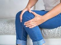 特写镜头少妇坐沙发和感觉的膝盖痛苦和嘘 免版税库存图片