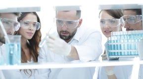 特写镜头工作在实验室里的医生药剂师和同事 免版税库存照片