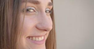 特写镜头年轻俏丽的白种人女性面孔侧视图射击与头发圆环的和闪烁与看的眼睛的构成 股票视频