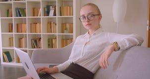 特写镜头年轻俏丽的白种人白肤金发的女实业家侧视图画象玻璃的使用看照相机的膝上型计算机 股票录像