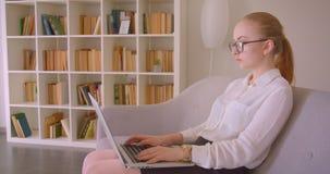 特写镜头年轻俏丽的白种人白肤金发的女实业家侧视图画象玻璃的使用膝上型计算机坐 股票视频