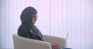特写镜头年轻可爱的回教使用坐在的膝上型计算机的女实业家和玻璃侧视图画象hijab的 股票录像