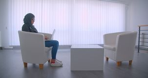 特写镜头年轻可爱的回教女实业家侧视图画象hijab和玻璃工作的在膝上型计算机坐 股票视频