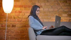 特写镜头年轻可爱的回教女性侧视图射击hijab的使用膝上型计算机,当坐长沙发户内时 股票视频