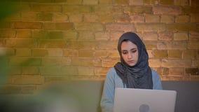 特写镜头年轻回教女性女实业家侧视图射击hijab的使用遥远的膝上型计算机和工作,当坐时 股票录像