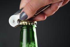 特写镜头年轻女性手开放绿色啤酒瓶 免版税库存照片