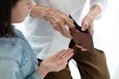 特写镜头年长妇女手捐零花钱的开放钱包、祖母或者监护人给孙女,亚洲女孩需求 免版税库存照片
