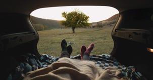 特写镜头录影加上在汽车等待的日落的树干的舒适袜子在自然的 4K 影视素材
