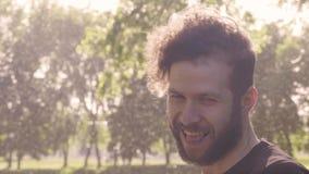 特写镜头微笑一个吸引人有胡子的人的半被转动的画象,看在凸轮和模仿 4K侧视图slowmo 影视素材