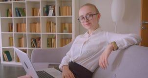 特写镜头快乐地微笑年轻俏丽的白种人白肤金发的女实业家侧视图画象玻璃的使用膝上型计算机 股票视频