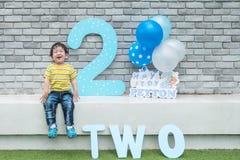 特写镜头愉快的亚洲孩子坐在砖墙背景的大理石长凳在第2个几年周年概念 免版税库存照片