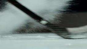 特写镜头慢动作冰球和飞行的雪,曲棍球运动员拾起顽童棍子 影视素材