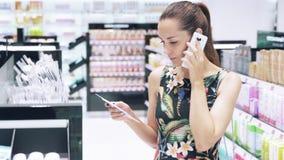 特写镜头慢动作射击一个女孩在香水商店选择她的构成,审查在架子的物品,谈话 股票视频