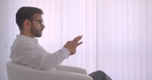 特写镜头成人英俊的有胡子的白种人商人侧视图画象在玻璃的使用坐在的片剂 影视素材