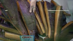 特写镜头手在商店窗口投入熏制的盐味的格林兰鲽在鱼市上 股票录像