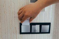 特写镜头手对打开的光的插入键卡片电子在酒店房间 在电子锁的酒店房间钥匙卡片在墙壁上 库存图片