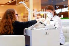 特写镜头手指由修指甲专家的钉子关心美容院的 修指甲师绘与指甲油的钉子 圣彼德堡 俄国 免版税图库摄影
