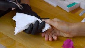 特写镜头手指由修指甲专家的钉子关心美容院的 修指甲师绘与指甲油的钉子 股票视频
