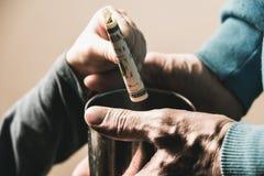 特写镜头手用一个叫化子无家可归的人和施舍美金的杯子肮脏的手  免版税图库摄影