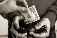特写镜头手用一个叫化子无家可归的人和施舍美金的杯子肮脏的手  免版税库存照片