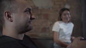 特写镜头打电子游戏的画象年轻人坐沙发在有逗人喜爱的smilling的女孩的顶楼样式屋子 股票视频