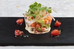 特写镜头把三文鱼沙拉切成小方块用鲕梨、蕃茄、葱、在washi的黑长方形石头板材供食的辣椒和香菜 免版税库存照片